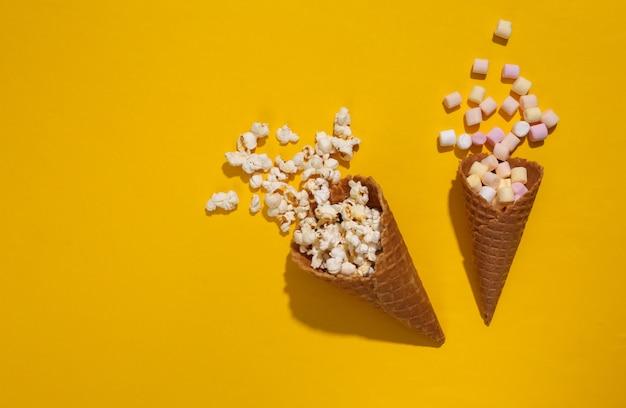 깊은 그림자가 있는 노란색 배경에 마시멜로와 팝콘이 있는 아이스크림 와플 콘, 탑 뷰, 플랫 레이, 팝 아트