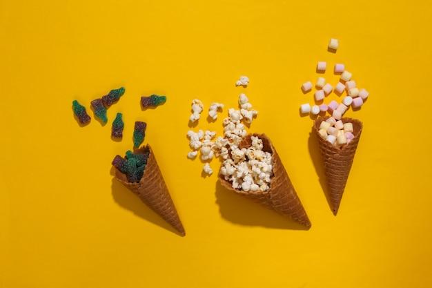 깊은 그림자가 있는 노란색 배경에 마시멜로, 젤리 캔디, 팝콘이 있는 아이스크림 와플 콘, 탑 뷰, 플랫 레이, 팝 아트