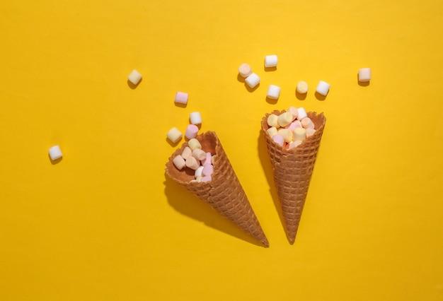 깊은 그림자가 있는 노란색 배경에 마시멜로가 있는 아이스크림 와플 콘, 탑 뷰, 플랫 레이, 팝 아트