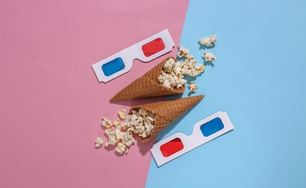 ポップコーン、深い影、上面図とピンクと青の明るいパステル調の背景に3dメガネとアイスクリームワッフルコーン。映画の時間。フラットレイ最小組成