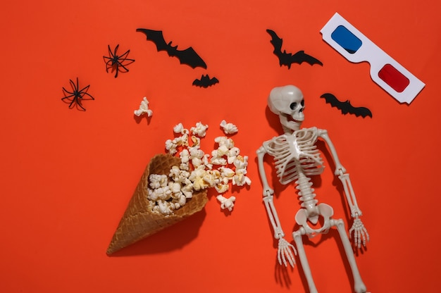 Ice cream waffle cones with popcorn, decorative bats and spiders, skeleton, 3d glasses on orange bright background. top view. scary movie. flat lay halloween composition