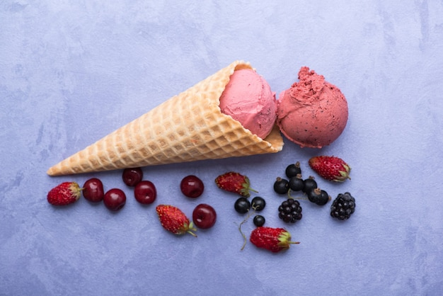 Ice cream with berries in a waffle horn on an ornamental purple background, top view