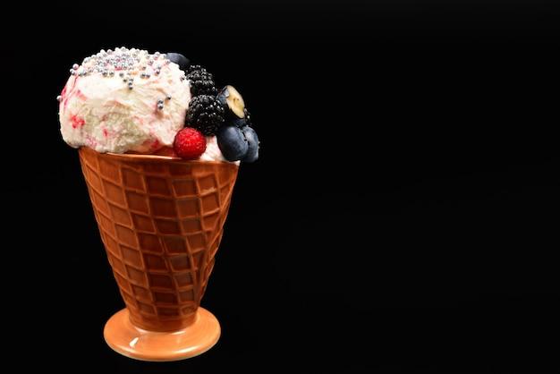 黒い壁にブルーベリー、ブラックベリー、ラズベリーのアイスクリーム。スペースをコピーします。