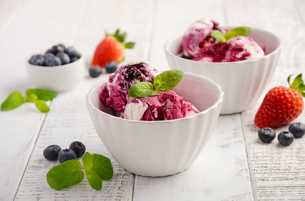 Ice cream with blueberries and strawberries in white bowl on a white wooden.