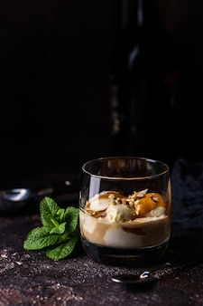 Мороженое с карамельной начинкой и ирландским сливочным ликером в стакане на темной поверхности.