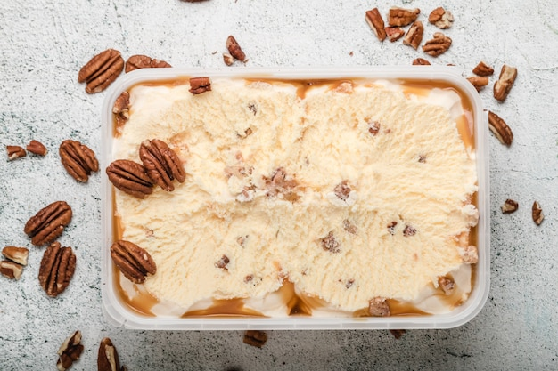Ice cream with ground nuts on white concrete table