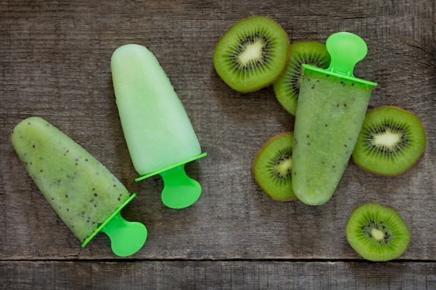 Ice cream with kiwi and fruit ice against a vintage wooden background, copy space.
