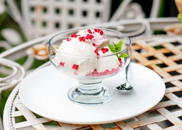 Мороженое с клубникой на столе в саду или уличном кафе