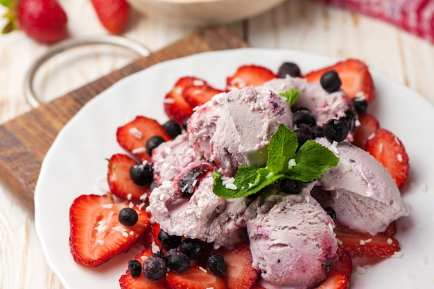 Ice cream with wild berries and strawberries