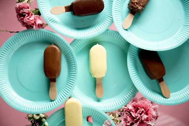 Мороженое на тарелках с цветком вокруг. летнее время или концепция вечеринки
