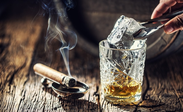 Ice cube being put into an ornamental cup of whisky placed on a old fashioned wood and burning cigar aside.
