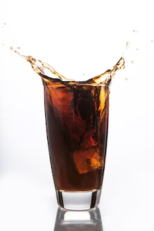 Ice cube falling into glass of soda
