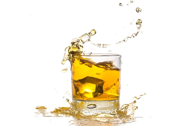 Ice cube falling into whiskey in glass
