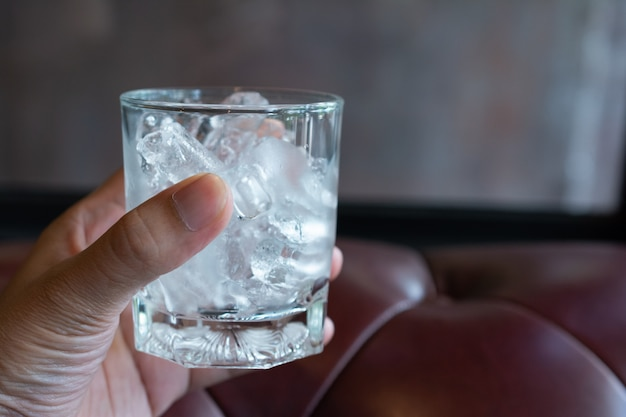 Ice cube in the glass with sofa wallpaper.