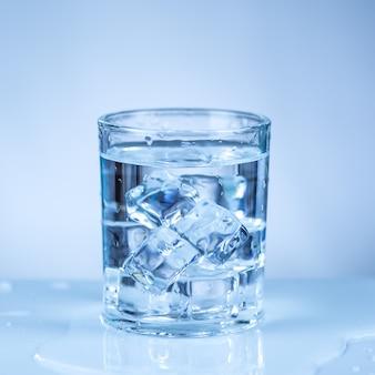 Кубик льда в стакане воды, изолированные на белой поверхности