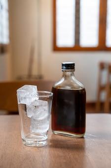 Кубик льда в стакане с холодным кофе на деревянном столе