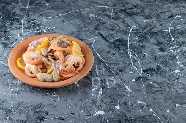 Кубик льда, нарезанные лимоны и креветки на тарелке рядом с солонкой на мраморном фоне.