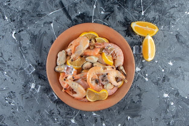 Ice cube, sliced lemons and prawns on a plate next to salt bowl , on the marble surface.