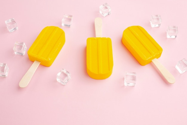 Ice cubes beside ice cream on stick