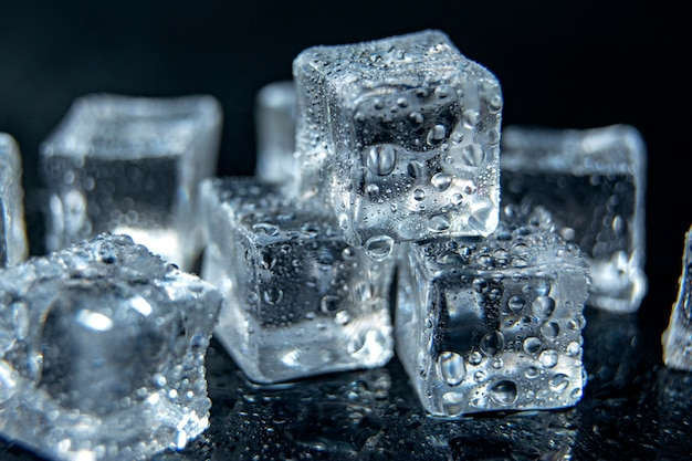 Ice cubes on black isolated glass background / ice cold concept