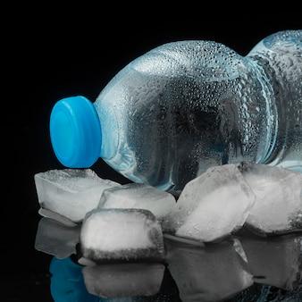 Cubetti di ghiaccio e bottiglia d'acqua vista frontale