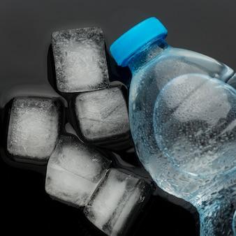 Cubetti di ghiaccio e una bottiglia di acqua vista dall'alto