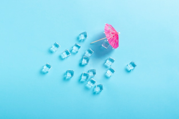 Ice cubes and a decorative umbrella for a cocktail on a blue surface. flat lay, top view