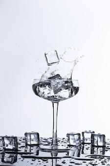 Кубики льда падают в стакан воды спалш