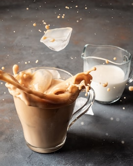 Ice cubes fall into a glass with coffee and milk raising a spray.