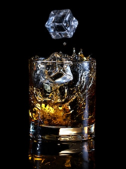 Ice cubes falling in glass of whiskey