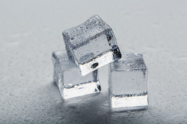 Ice cubes in the form of a pyramid with water drops close - up in macro on a white background.