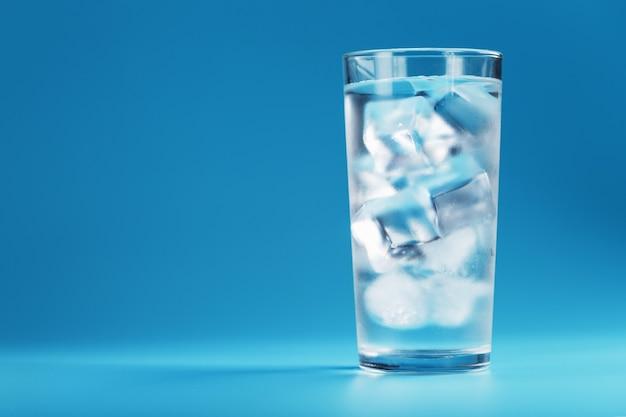 青い背景に透き通った水とガラスの角氷。暑い日にはさわやかで健康的な水
