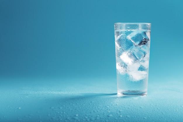 青い背景に透き通った水とガラスの角氷。