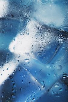 青い背景にさわやかな氷水とガラスの角氷