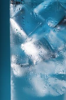 氷水のクローズアップマクロの滴と霧のガラスの角氷。暑い時期にはさわやかで冷たい飲み物。青い表面。全画面表示