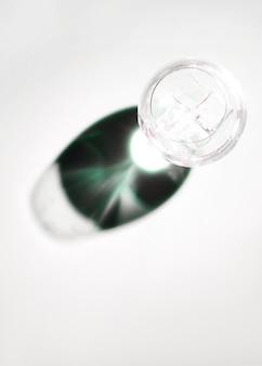 Кубики льда в прозрачной рюмке с темной блестящей тенью на белом фоне