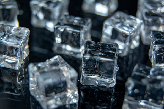 Ice cubes / a lot of different ice cubes on reflection table on black background