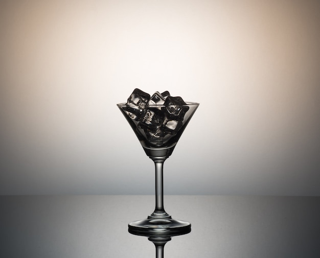 Ice cubes in martini glass .