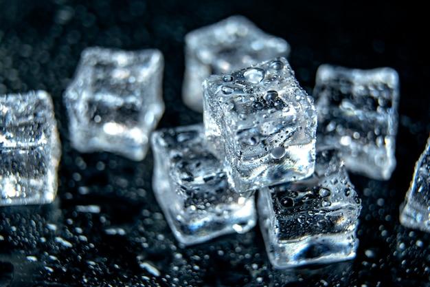 Ice cubes / melting ice cubes on black background, close up