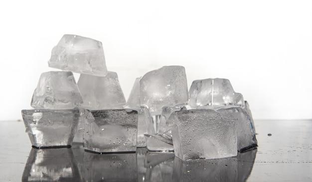 Кубики льда тают на темной отражающей поверхности, белый фон, выборочный фокус.