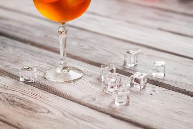 와인잔 근처에 있는 얼음 조각. 나무 표면에 유리입니다. 상쾌한 여름 음료. 휴식을 취하는 데 필요한 모든 것.