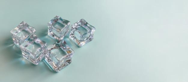 Кубики льда на ярко-синем фоне летней концепции