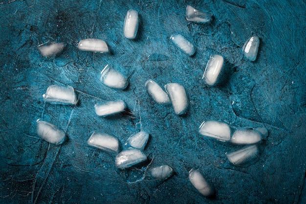 어두운 푸른 돌 표면에 얼음 조각입니다. 평평한 평면도, 평면도
