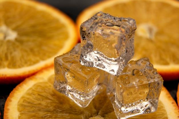 Кубики льда на оранжевый. оранжевый фон капли воды