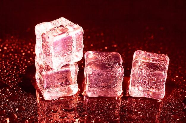 赤い光を反射するアイス キューブ。