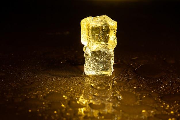 黄色い光を反射するアイス キューブ。