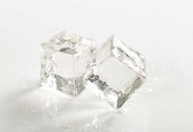 Кубики льда на белом столе