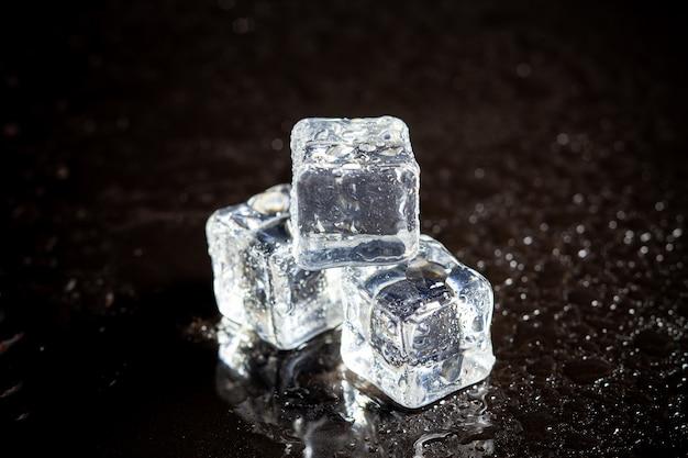 黒いテーブルの背景に角氷の反射。
