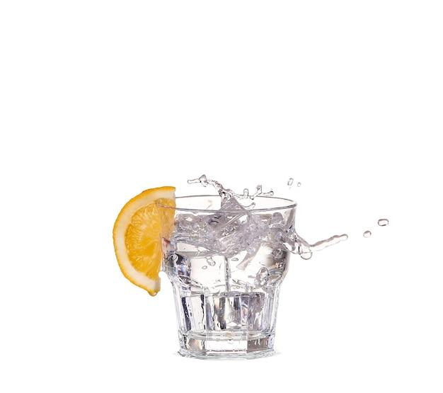 白で隔離の水のガラスに飛び散る角氷