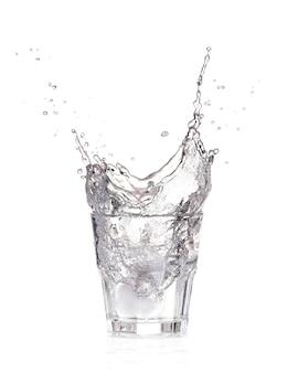 白で隔離され、水のガラスにはねかけるアイスキューブ
